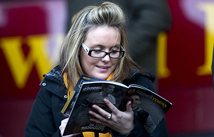 Image of a 'Well fan reading the matchday programme